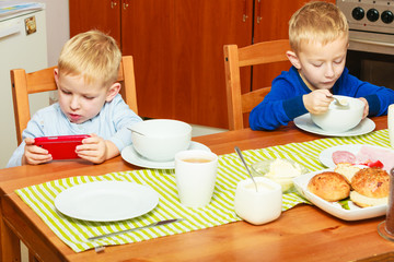 Two boys children eating breakfast at home