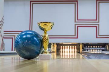 Closeup of blue bowling ball near golden trophy on the floor