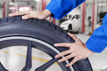 Mechanic hands pushing tire at workshop