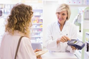 Pharmacist using card machine