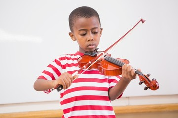 Focus pupil playing violin in classroom