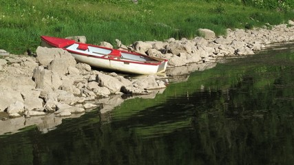 Little row boat on the shore of a lake