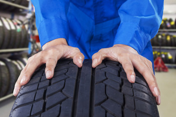 Mechanic holding a tire in vehicle shop