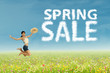 Woman jumps with spring sale clouds