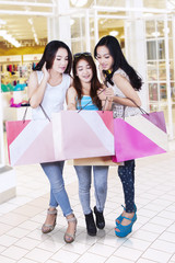 Young shoppers looking shopping bag