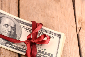 dollars wraped up with a red ribbon isolated on white background