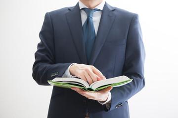 書籍を参照するビジネスマン