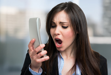 Angry businesswoman yelling on the phone