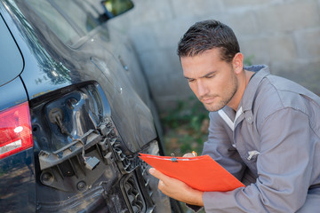 Mechanic inspecting damaged car