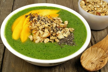 Green smoothie bowl close up on wood