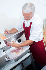 Butcher slicing meat