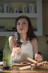 Woman eating homemade pizza and drinking red wine