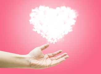 Glowing Cloud heart shape are floating on open woman hand on pin