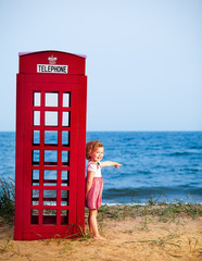 Portrait of a little girl standing near public telephone booth.