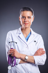 Portrait of young female doctor holding a stethoscope, isolated