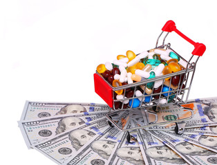 Shopping cart full with pills over dollar bills, isolated