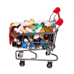 Shopping cart full with pills and capsules isolated
