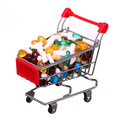 Shopping cart full with pills and capsules isolated on white