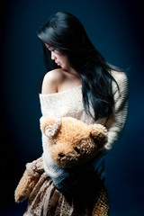 Portrait of a sad asian girl with her Teddy bear