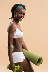 Woman with dumbbells and yoga mat