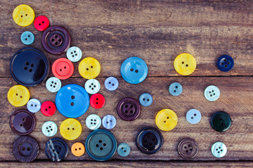 Lots of colorful buttons for clothes on wooden background.