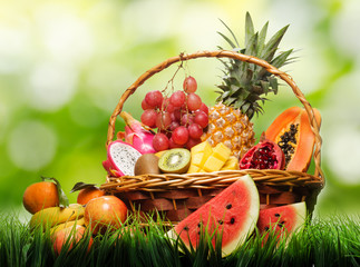 Basket of fresh tropical fruits on green grass and on nature bac