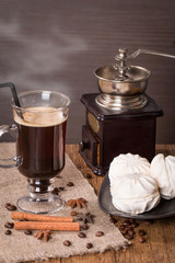 Coffee in glass cup and cinnamon with zephyr