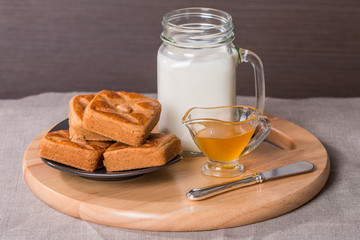 Fresh milk in glass and sweet cookies with honey