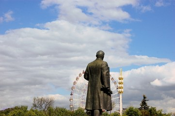 Lenin statue looking at Ferris wheel, Moscow, Russia.