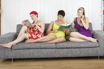 Drei junge Frauen auf dem Sofa, Tablet-PC, Buch und Handy