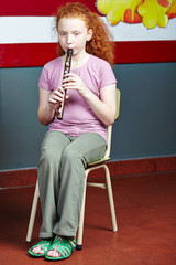 Girl playing flute in music lessons