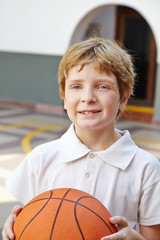 Child with basketball in physical education class