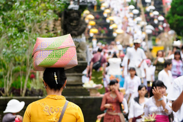 The woman is carrying gifts for Hindu gods on the head