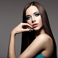 Beautiul elegant woman with turquoise make-up and long hairs
