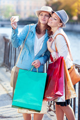 Two beautiful girls with shopping bags taken picture of themself