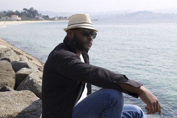 black pensive man looking out to sea
