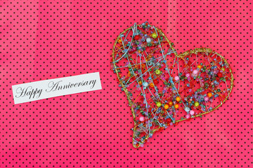 Happy Anniversary card with heart made of colorful beads on pink