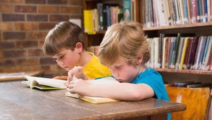 Cute pupils reading in library