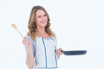 Smiling woman holding frying pan and wooden spoon