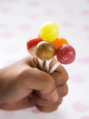 hand holding a bunch of the lollipop
