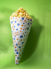 cup of the pop corn on the green background