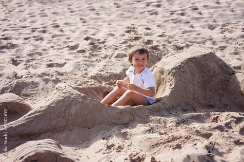 Adorable kid, playing on the beach Poster