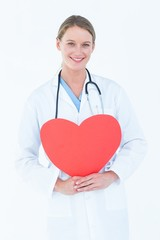 Doctor holding red heart card