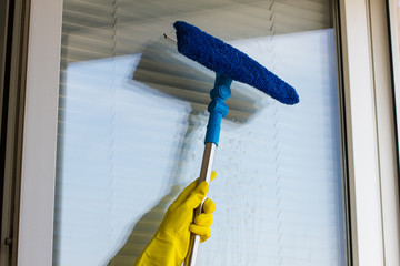Cleaning windows  in yellow gloves