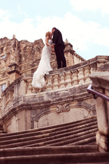 groom and bride kissing on top of stairs