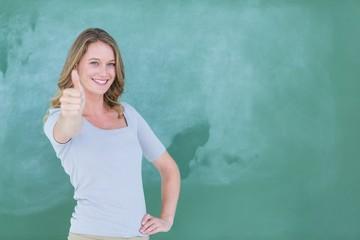 Smiling teacher standing thumbs up in front of blackboard