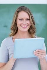 Smiling teacher holding tablet pc