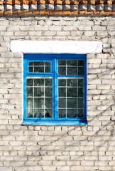 blue frame window in a brick wall