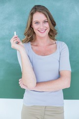 Woman in front of a blackboard holding a piece of chalk