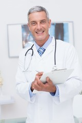 Happy doctor holding clipboard and smiling at camera